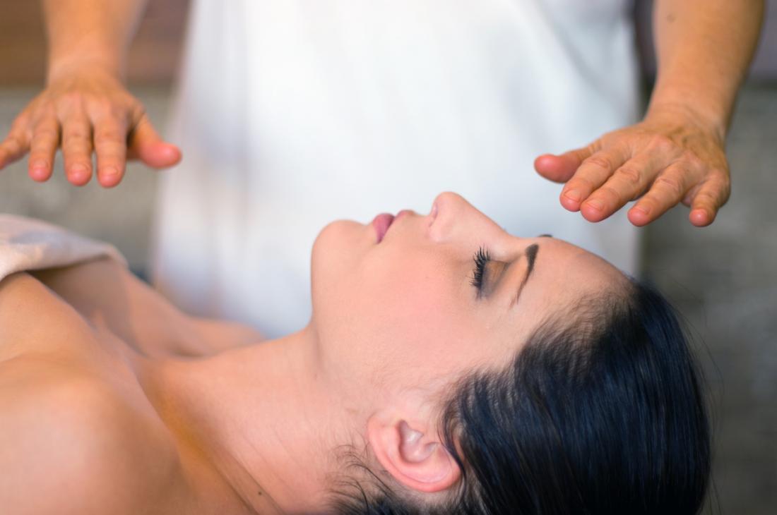 En Reiki, le praticien transfère de l'énergie en plaçant ses mains sur ou sur le patient.