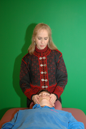 praticienne de reiki plaçant ses mains sur la tête d'un client allongé